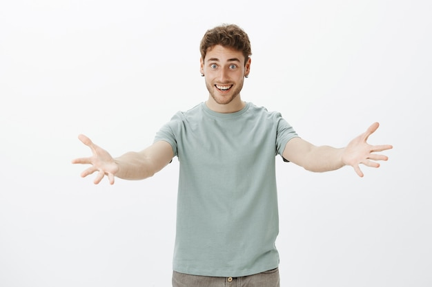 Come to me, let me cuddle you. portrait of cute friendly-looking man in casual outfit, pulling arms towards and smiling broadly