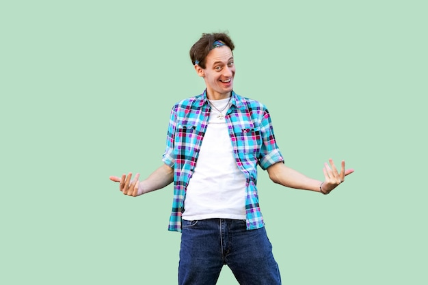 Come to me. portrait of funny young man in casual blue checkered shirt and headband standing looking at camera and inviting to come to him with toothy smile. studio shot, isolated on green background.