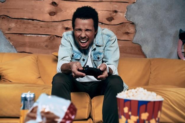 いい加減にして!ビデオゲームをプレイし、家で時間を過ごしながら顔を作るカジュアルな服装で欲求不満の若い男