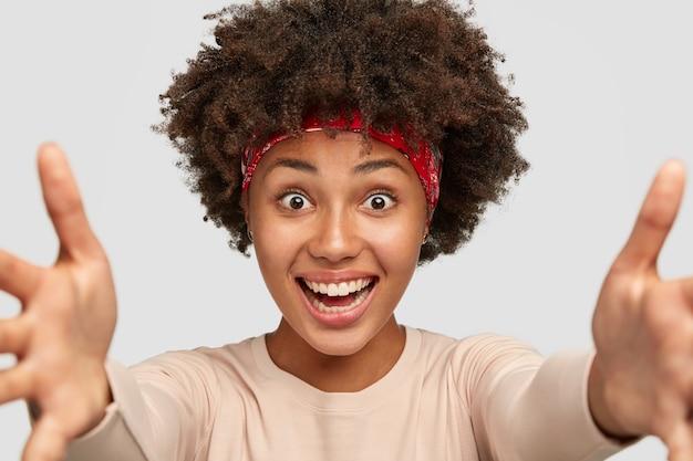 Иди ко мне. взволнованная счастливая афро-женщина тянет руки к