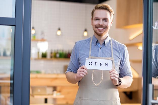 私たちのカフェに来てください。あなたに微笑んで、顧客を招待しながらラベルタグを保持している幸せな喜びのフレンドリーな男