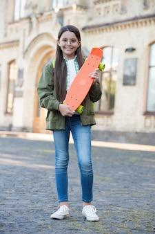 스케이트를 타러 오세요. 행복한 아이가 페니 보드를 잡고 있습니다. 작은 스케이팅 도시 야외. 운송용 보드. 레크리에이션 활동. 액션 스포츠. 여행과 모험. 스트리트 스케이트보드.