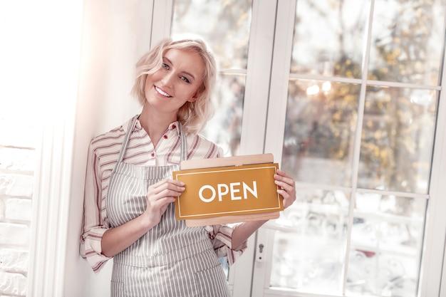 私たちに来てください。カフェに訪問者を招待しながらオープンサインを持って喜んで幸せな女性