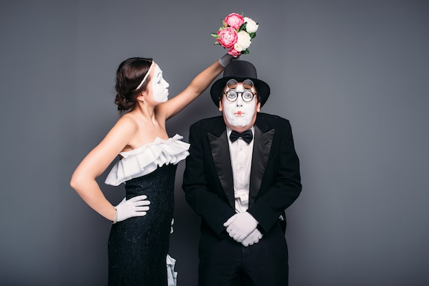 Comedy actor and actress posing with flower bouquet. mime theater performers posing. p