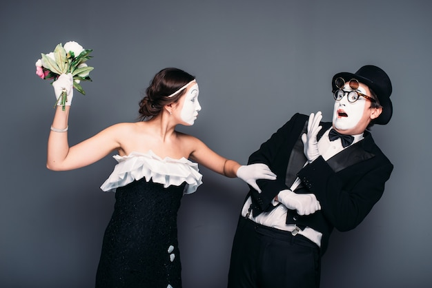 Comedy artists performing with flower bouquet. mime theater performers posing.