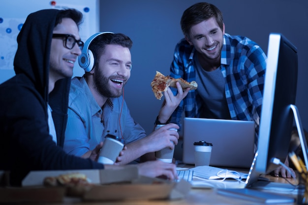 Comedy movie. happy positive male friend watching a film on the computer and laughing while eating pizza