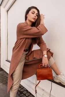 아름 다운 매력적인 젊은 여성 패션 베이지 색 바지에 아름 다운 우아한 코트 가죽 핸드백과 세련 된 신발 도시에서 벽 근처에 달려있다. 고급 귀여운 유행 소녀가 머리카락을 곧게 만듭니다. 세련된 뷰티 레이디