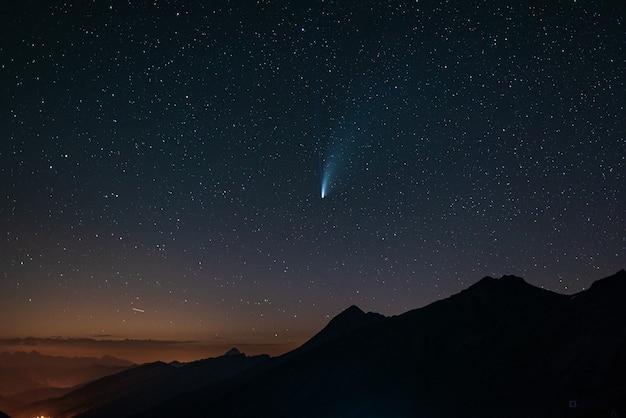 Двойные хвосты кометы neowise светятся в ночном небе. телеобъектив, детали двух звездных троп