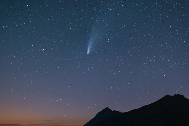 Comet neowise twin tails glowing in the night sky. telephoto view, details of the two star trails.
