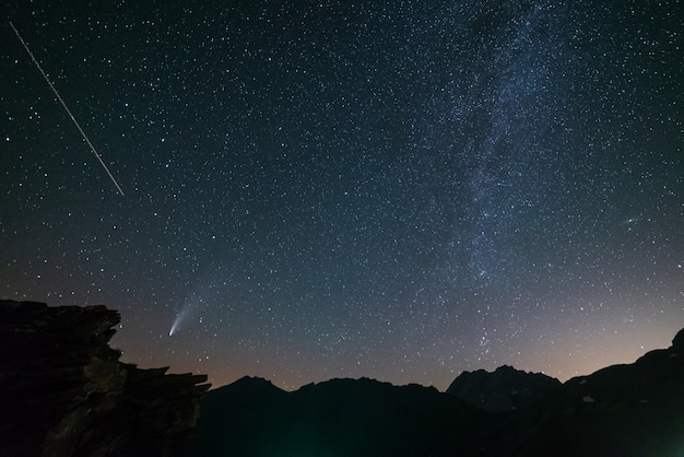 Comet neowise twin tails glowing in the night sky. telephoto view, details of the two star trails
