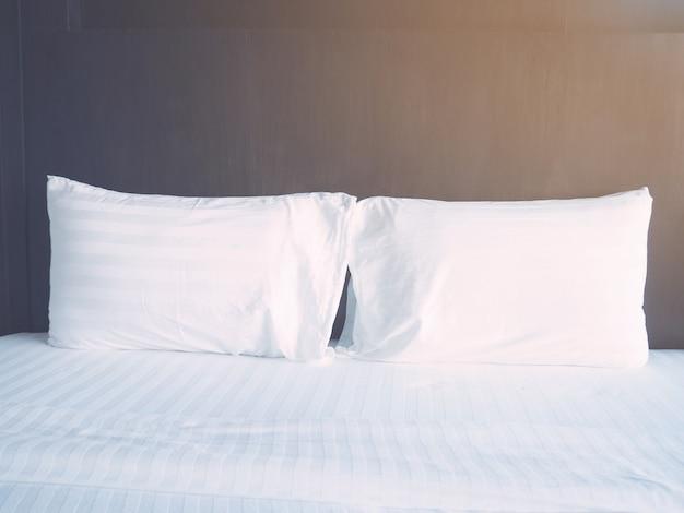 Комфортная спальня по утрам. закройте подушки на кровати у окна с солнечным светом, мягкий стиль