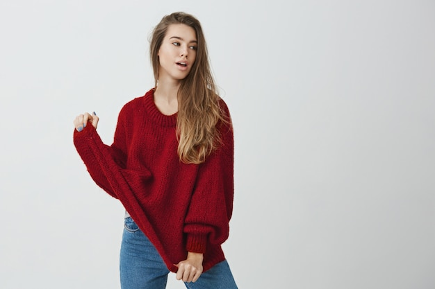 Comfort before fashion. portrait of feminine gorgeous caucasian woman looking aside with sensual expression and pulling sweater with hands, posing like model for magazine or online-store