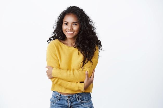 快適さ、ロマンス、居心地のよさのコンセプト。白い壁の上の愚かなカメラを笑顔で快適に感じるように体を抱きしめて、自分自身を抱き締める黄色いセーターの陽気な素敵なアフリカ系アメリカ人の女の子