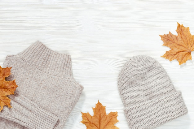 Comfort warm outfit for cold weather. knitted grey pullover and warm beautiful cap on white wood decorated autumnal yellow leaves. top view. flat lay.
