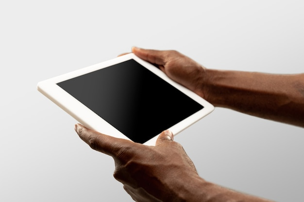 Comfort watching. close up male hands holding tablet with blank screen during online watching of popular sport matches, championships. copyspace for ad. devices, gadgets, technologies concept.