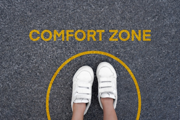 コンフォートゾーンのコンセプト。円の線をまたいでください。フットウォーキングシューズの上面図。床の道路の背景に立っている子。