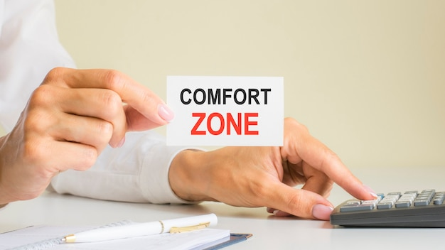 Comfort zone, message on business card shown by woman pressing calculator key at workplace in light office, selective focus, business and financial concept