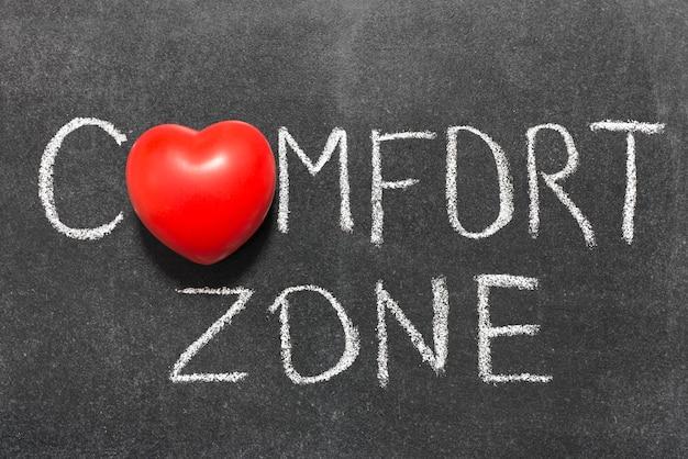 Фраза зоны комфорта, написанная от руки на доске с символом сердца вместо o
