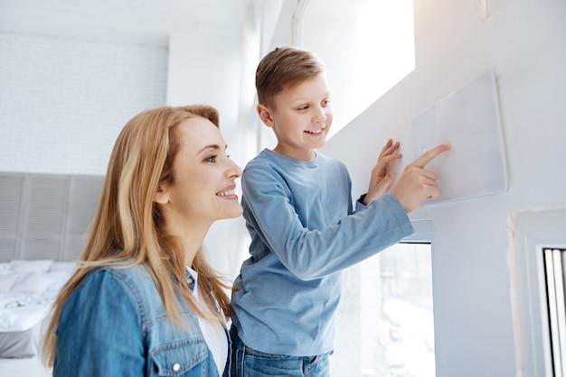 Комфортная квартира. радостная счастливая милая женщина, стоящая вместе с его матерью и использующая панель управления, живя в умном доме