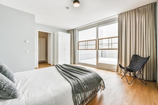 モダンなアパートメントの明るいベッドルームのバルコニーのドアと窓の近くにある快適なベッドと椅子