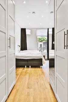 현대 아파트의 창문에 흰색 벽과 검은 색 커튼이있는 작고 좁은 미니멀 한 스타일의 침실에 편안한 침대와 램프 배치