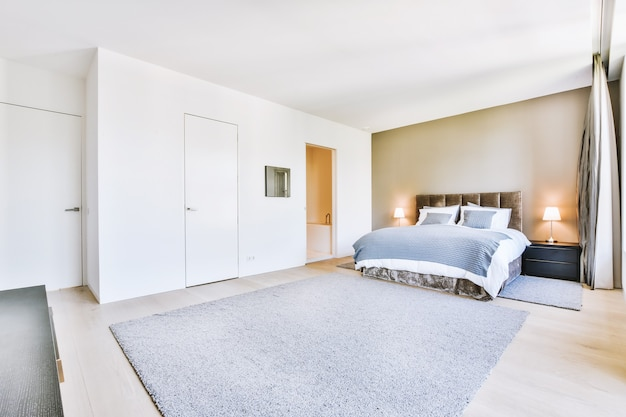Удобная кровать и мягкий ковер в просторной спальне с интерьером в стиле минимализм.