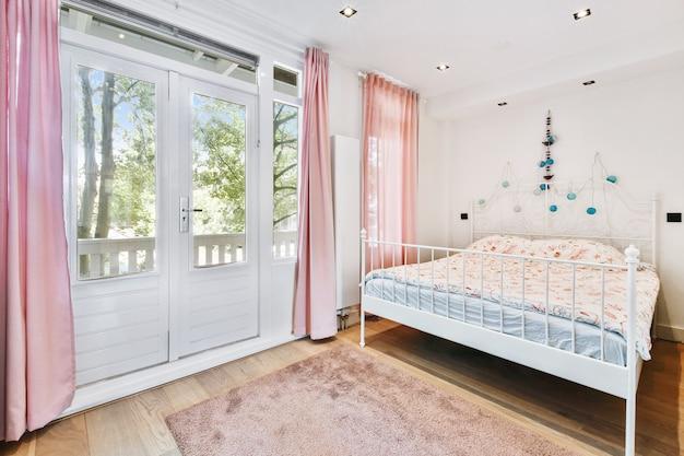 Удобная кровать возле балконной двери с занавесками в уютной светлой спальне дома.