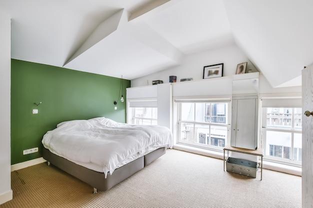 Удобная кровать у зеленой стены в мансардной спальне в современном минималистском стиле с окнами.