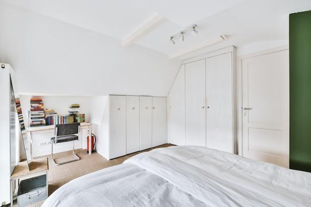 Удобная кровать у зеленой стены в мансардной спальне в современном минималистском стиле.