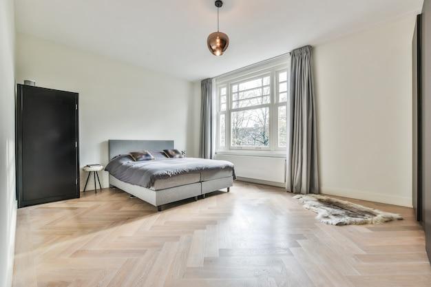 Удобная кровать у окна в углу светлой просторной спальни с мебелью в стиле минимализм в современной квартире.