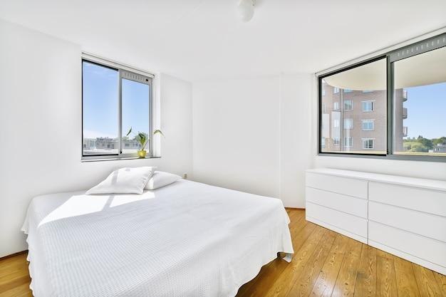 현대 아파트의 넓은 침실에 담요와 베개가있는 편안한 침대