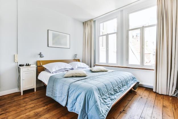 현대 아파트의 넓은 침실에서 램프와 의자 근처에 담요와 베개가있는 편안한 침대
