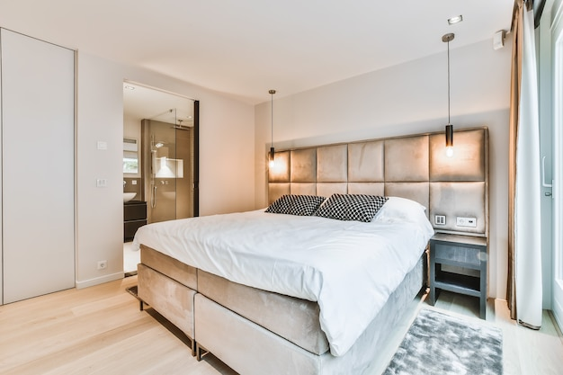 Comfortable bed with blanket and pillows located near lamps and chair in spacious bedroom in modern apartment