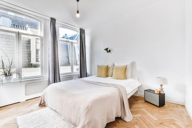 Comfortable bed with blanket and pillows in spacious bedroom in modern apartment