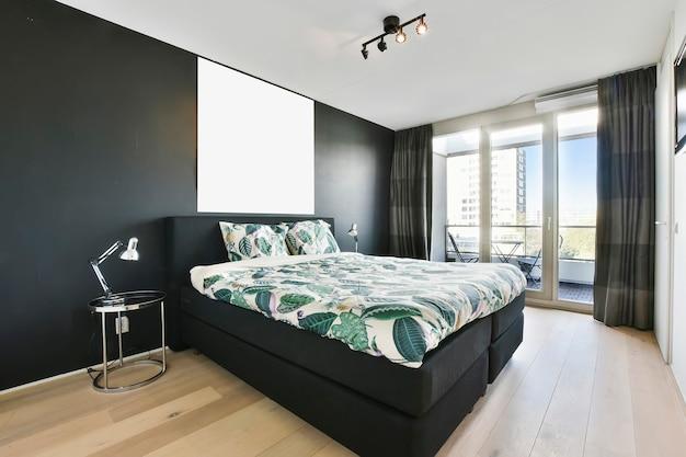 현대 아파트의 세련된 침실에 빈티지 사진이있는 회색 벽 근처에 장식용 이불과 베개가있는 편안한 침대