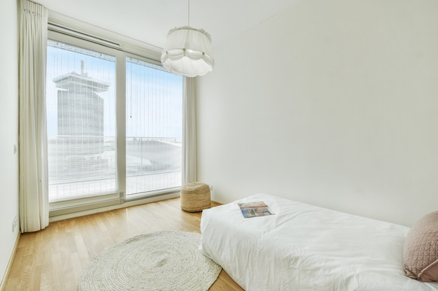 Comfortable bed with pillow and magazine located in light bedroom with white wall and large window in modern apartment