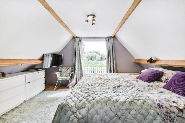 自宅の明るい屋根裏部屋の寝室のカーテン付きの窓に対して椅子とテレビの近くに配置された枕と毛布付きの快適なベッド