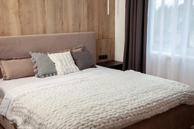 Удобная кровать с подушками в номере. стильный дизайн интерьера