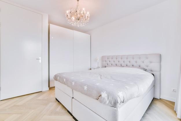 침실의 고급 샹들리에 아래에 부드러운 담요와 나무 침대 옆 탁자가있는 편안한 침대