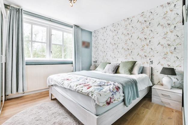 Удобная кровать с мягкими подушками и пледом у стены с растительным орнаментом и окном с занавесками в светлой спальне дома.