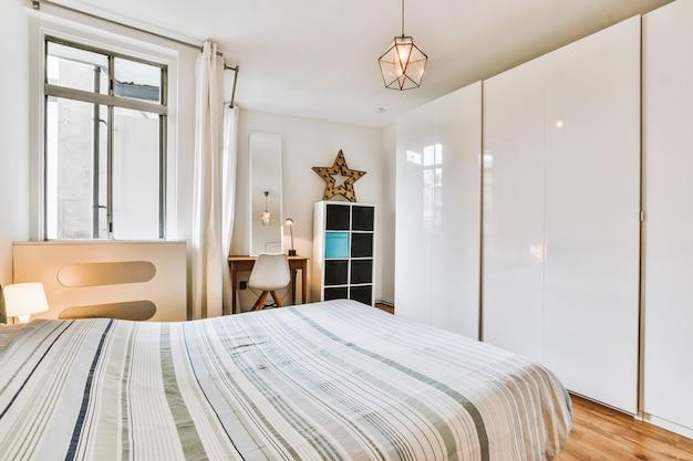 현대 아파트의 밝은 침실에 의자가있는 책상과 수납 가구 근처에 스트라이프 담요가있는 편안한 침대