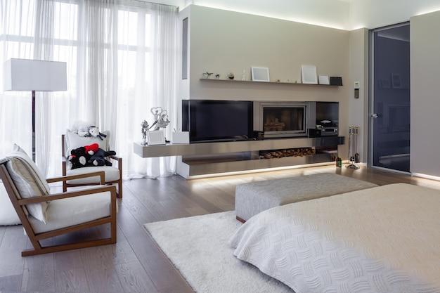 Комфортная спальня с широким окном и встроенным камином.