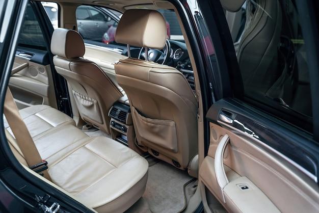 Комфортные бежевые кожаные сиденья и панель управления кондиционером заднего сиденья пассажира