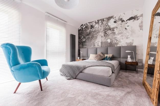 Удобное синее кресло в спальне, стоящее рядом с двуспальной кроватью с подушками, и статуя волка, стоящая на ночном столике, отражается в гигантском зеркале.