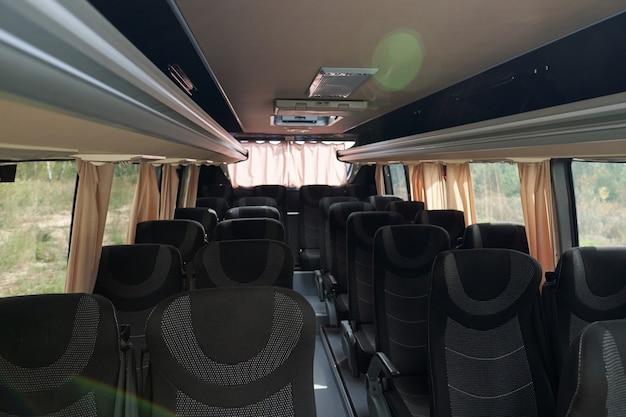 Комфортабельный автобус с верхними отсеками под тканевыми сиденьями и занавесками на окнах.