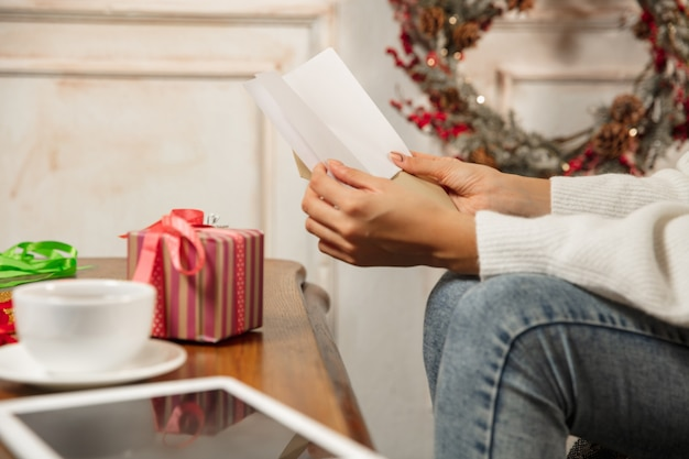 Комфортный. крупным планом женские руки открываются, получая поздравительную открытку на новый год и рождество 2021 года от друзей или семьи. читаем письмо с наилучшими пожеланиями, открываем конверт. праздники, торжество.
