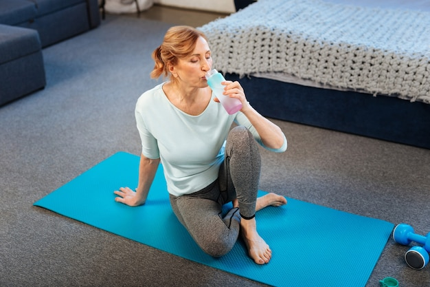 Comfortable clothes. peaceful fit lady in leggings resting on sportive mat and drinking fresh water after intense training