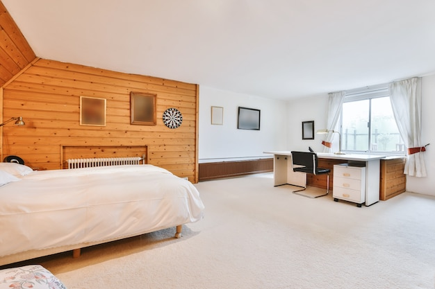 Comfortable contemporary bed located near retro cabinet and chair in light bedroom with bathroom doorway at home