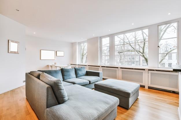 モダンなアパートメントの明るいリビングルームにあるテレビと装飾が施された本棚の近くにある快適なソファ