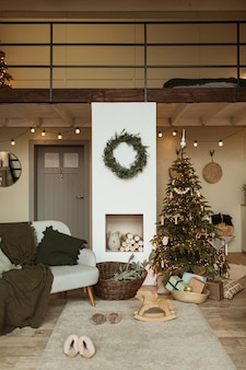 Comfortable cozy living room decorated with christmas tree with gifts, wreath frame, fireplace, sofa, carpet.